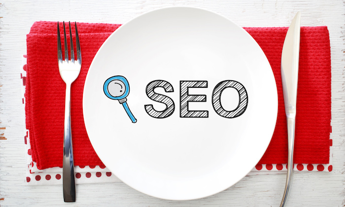 SEO concept on white plate with fork and knife